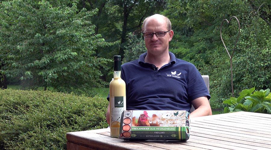 Farmer Sven Sangel with a bottle of egg liqueur and an egg box